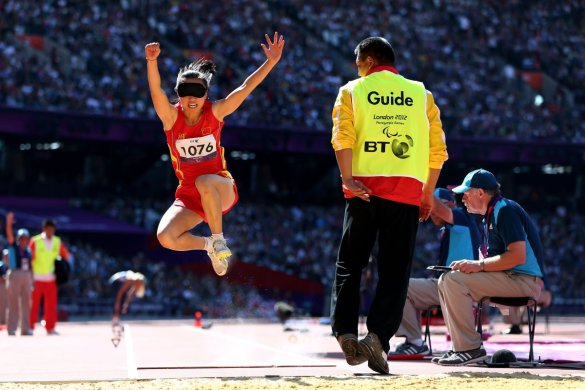 juntingxian jia participates-in-the-long-jump-with-the-help-of-her-guide