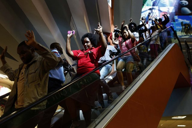 Civilians escape an area at the Westgate Shopping Centre. (Photo by Siegfried Modola/Reuters)