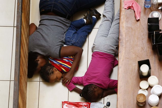 A mother and her children hide from gunmen inside the mall. (Photo by Siegfried Modola/Reuters)