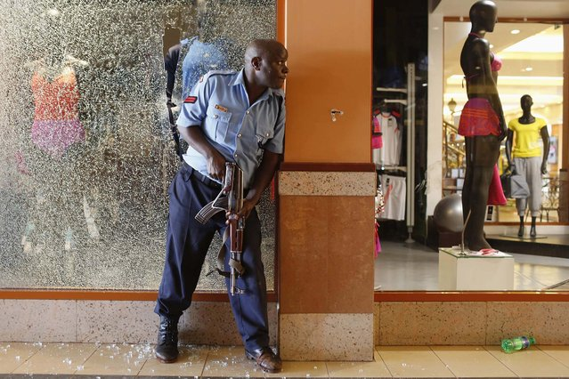 A police officer tries to secure an area inside the Westgate Shopping Centre. (Photo by Siegfried Modola/Reuters)