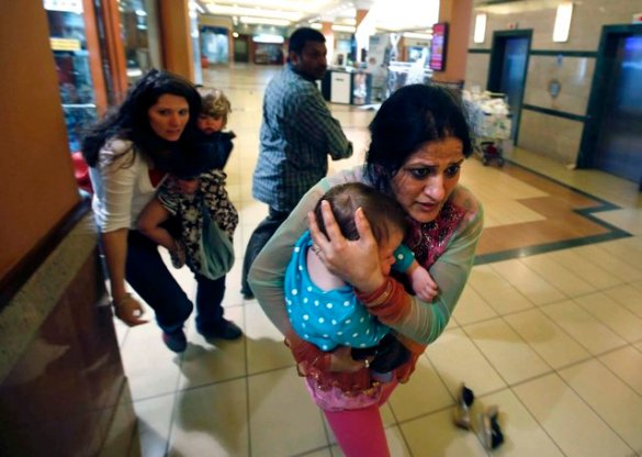 Women carrying children run for safety in the mall. (Photo by Goran Tomasevic/Reuters)