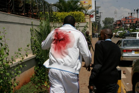 A wounded man is escorted outside the Westgate Mall, an upscale shopping mall in Nairobi, Kenya Saturday September 21 2013, where shooting erupted when armed men attempted to rob a shop, according to police. Witnesses say a half dozen grenades also went off along with volleys of gunfire in and around the mall. (Photo by AP Photo)