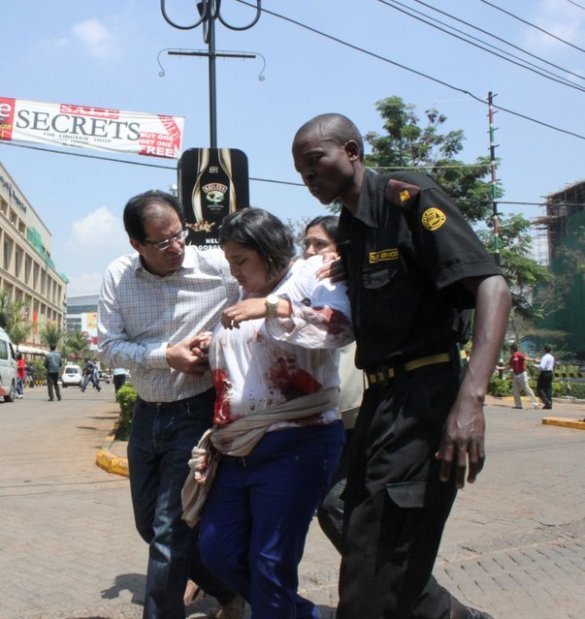 A security officer helps a wounded woman outside the Westgate Mall in Nairobi, Kenya on Saturday, September 21 2013, after gunmen threw grenades and opened fire during an attack that left multiple dead bodies and dozens wounded. (Photo by Jason Straziuso/AP Photo)