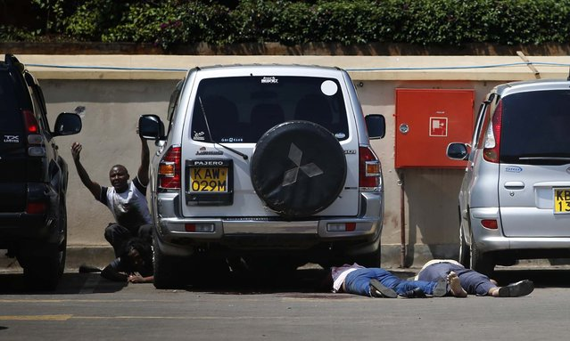 People come out from hiding under a car next to bodies in the mall's parking lot. (Photo by Goran Tomasevic/Reuters)
