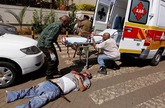Rescuers attempt to evacuate a man injured in the shootout. (Photo by Thomas Mukoya/Reuters)