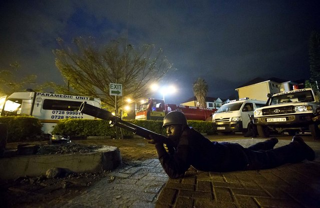 A police officer takes cover outside the Westgate Mall as the search for the gunmen continues. (Photo by Ben Curtis/Associated Press)