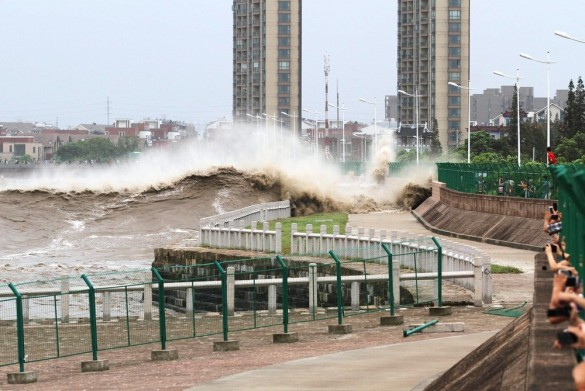 A tidal wave hits a bank along the Qiantang River on August 22, 2013 in Haining, China. The 12th typhoon Trami landed in Fujian province at 2:40 am and led gales and heavy rainfalls in east China. (Courtesy: ChinaFotoPress)