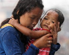 A Filipino woman holding a baby runs during a downpour in the super typhoon devastated city of Tacloban, Leyte province, Philippines, 12 November 2013. International aid poured in for the Philippines as authorities stepped up efforts to reach survivors driven to looting after one of the world's strongest typhoons devastated their towns. A tropical depression brought heavy rains over the central and eastern Philippines, where provinces badly hit by Haiyan are located, raising concerns that relief operations would be hampered. (Photo by Francis R. Malasig/EPA)