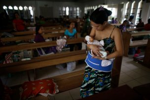 A mother breastfeeds her baby inside a chapel which was turned into a makeshift hospital after Super Typhoon Haiyan battered Tacloban city in central Philippines November 13, 2013. (Photo by John Javellana/Reuters)