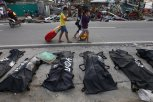 People cover their noses from the stench of dead bodies in an area affected by Typhoon Haiyan in Tacloban, Philippines, Wednesday, November 13, 2013. (Photo by Dita Alangkara/AP Photo)