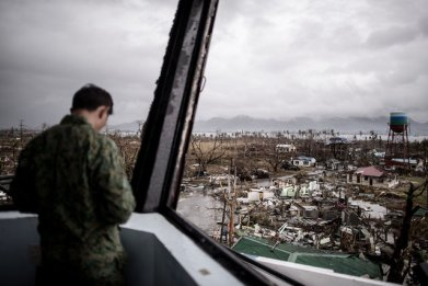 A Filipino military personnel stands in the damaged control tower of the airport in Tacloban, on the eastern island of Leyte on November 12, 2013 after Super Typhoon Haiyan swept over the Philippines. (Photo by Philippe Lopez/AFP Photo)