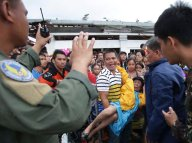 Filipino troopers control survivors who want to board military planes to flee the typhoon ravaged Tacloban city, Leyte province, central Philippines on Tuesday, November 12, 2013. (Photo by Aaron Favila/AP Photo)