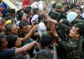 Typhoon survivors jostle to get a chance to board an evacuation flight on a C-130 military transport plane Tuesday, November 12, 2013, in Tacloban, central Philippines. (Photo by Bullit Marquez/AP Photo)