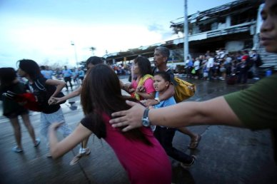 Survivors of Typhoon Haiyan are stopped by rescue workers as they try to board a C-130 cargo plane at the airport in Tacloban city, Leyte province, central Philippines, Tuesday, November 12, 2013. (Photo by Wong Maye-E/AP Photo)