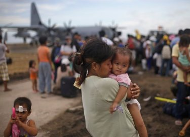 A woman survivor of Typhoon Haiyan weeps as she holds her daughter while waiting for her turn to get on a U.S. Air Force plane to leave for the capital city of Manila, at the airport in Tacloban, central Philippines, Wednesday, November 13, 2013. (Photo by Dita Alangkara/AP Photo)
