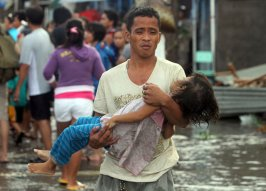 A father carries the lifeless body of his daughter on the way to the morgue after super typhoon Haiyan hit Tacloban City in Leyte province, central Philippines November 10, 2013. (Photo by Nino Jesus Orbeta/Reuters/Philippine Daily Inquirer)