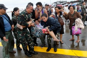 Military personnel carry a woman after she fainted while waiting in line to leave the town on military air transport, at the destroyed airport after super typhoon Haiyan battered Tacloban City, in central Philippines November 12, 2013. (Photo by Edgar Su/Reuters)