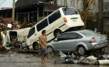 A woman walks past stacked up vehicles in Tacloban, eastern island of Leyte in November 12, 2013. (Photo by Noel Celis/AFP Photo)