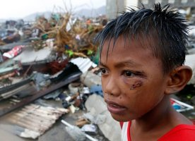 A boy who was wounded by flying debris due to Super Typhoon Haiyan stays at the ruins of his family's house in Tacloban city November 10, 2013. (Photo by Erik De Castro/Reuters)