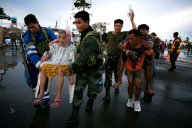 An elderly woman and an injured man are carried to a waiting C130 aircraft during the evacuation of hundreds of survivors of Typhoon Haiyan on Tuesday in Tacloban. (Photo by Paula Bronstein/Getty Images)