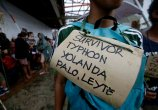 Typhoon survivors hang signs from their necks as they queue up in the hopes of boarding a C-130 military transport plane Tuesday in Tacloban. (Photo by Bullit Marquez/Associated Press)