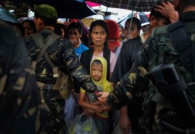 Locals, cordoned off by security forces, seek transportation out at the airport in Tacloban. (Photo by Jes Aznar/The New York Times)
