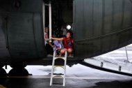 Residents aboard a government plane wait for family members, before leaving the devastated city of Tacloban. (Photo by Jes Aznar/The New York Times)