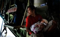 Manuel Aballe holds his 2-month-old daughter Richelyn inside a government plane waiting to leave Tacloban. (Photo by Jes Aznar/The New York Times)