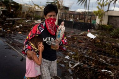 People carry their belongings through the streets of Tacloban o Tuesday. (Photo by Jes Aznar/The New York Times)