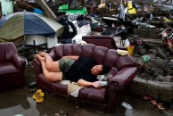 A typhoon victim rests on a sofa at the ruins of her family's home in Palo, Leyte province, on November 12, 2013. (Photo by Erik De Castro/Reuters)