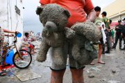 A survivor carries her daughter's stuffed teddy bears near Tacloban on Tuesday. (Photo by Jeoffrey Maitem/Getty Images)
