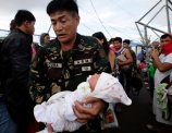 A soldier carries one-day-old baby Ian Daniel Honrado to a waiting military transport plane Wednesday November 13, 2013 from the damaged Tacloban airport at Tacloban city, Leyte province in central Philippines. (Photo by Bullit Marquez/AP Photo)