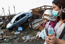 People covering their faces pass a car in debris after super typhoon Haiyan battered Tacloban City, in central Philippines November 13, 2013. Philippine officials have been overwhelmed by Haiyan, one of the strongest typhoons on record, which tore through the central Philippines on Friday and flattened Tacloban, coastal capital of Leyte province where officials had feared 10,000 people died, many drowning in a tsunami-like wall of seawater. (Photo by Edgar Su/Reuters)
