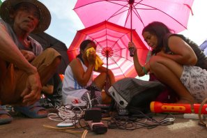 Typhoon survivors queue up to have their mobile phones charged using power outlets provided by a cellular service provider in Tacloban, central Philippines, Wednesday, November 13, 2013. (Photo by Dita Alangkara/AP Photo)